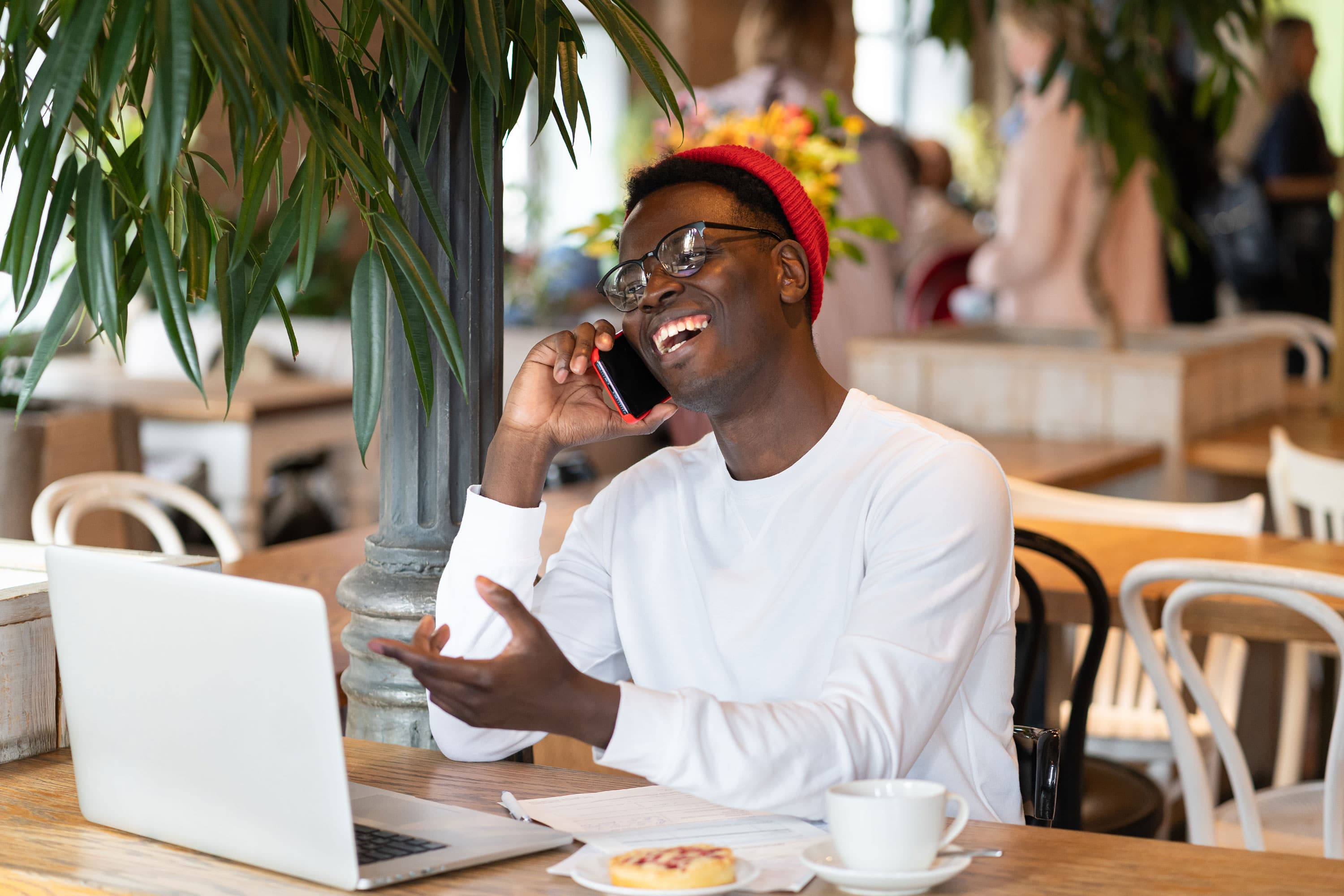 Man at coffee shop talking on phone to signify how happy you'll be when you find high-paying clients on Upwork